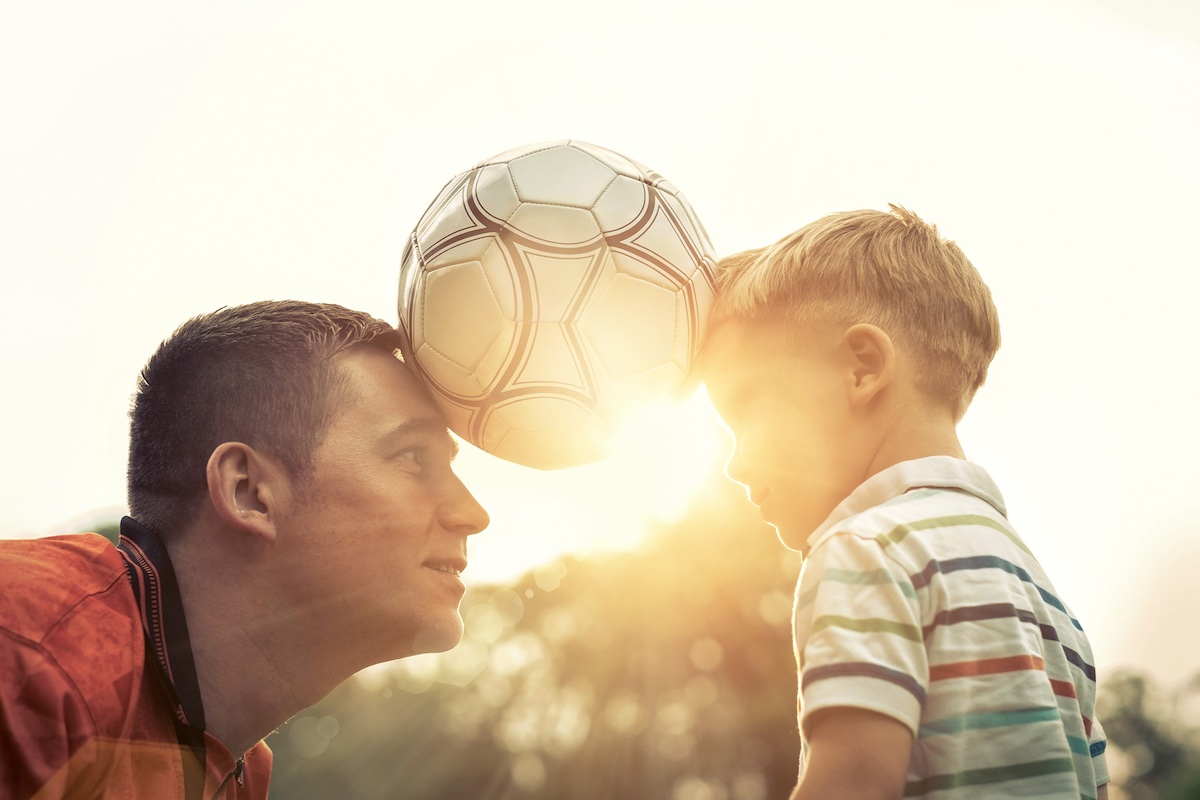 Bilde av far og sønn med en fotball mellom pannene sine.