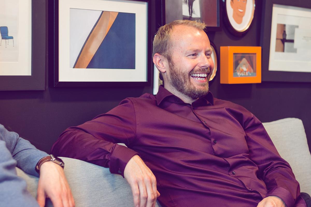 Karl Erik Lohr smiler i sofaen til Media Sør