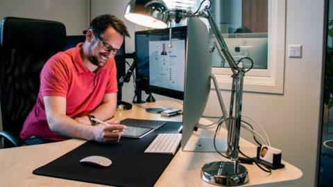 Remi A. Netteland smilende paa kontorpulten